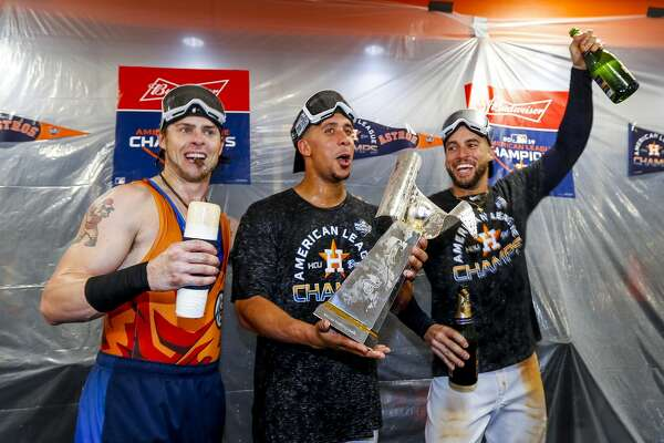 Houston Astros right fielder Josh Reddick (22), Houston Astros left fielder Michael Brantley (23) and Houston Astros center fielder George Springer (4) celebrate in the clubhouse after the Astros won the American League Championship Series at Minute Maid Park in Houston on Saturday, Oct. 19, 2019.