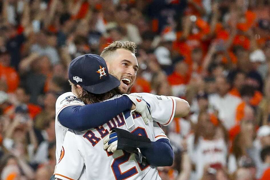 Houston Astros center fielder George Springer (4) and Houston Astros right fielder Josh Reddick (22) hug after the Astros win the American League Championship Series at Minute Maid Park in Houston on Saturday, Oct. 19, 2019.