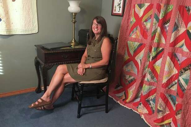 Godfrey homeowner Angela MacDowell sits in her home's study, which until recently was her son Matt MacDowell's bedroom. Angela's great aunt's quilt, right, covers a closet, now filled with games, but which Angela decided to make a supply closet for supplies for scrapbooking and creating artwork.