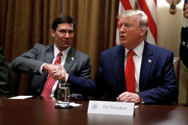 President Donald Trump shakes hands with Defense Secretary Mark Esper during a briefing with senior military leaders in the Cabinet Room at the White House in Washington, Monday, Oct. 7, 2019.