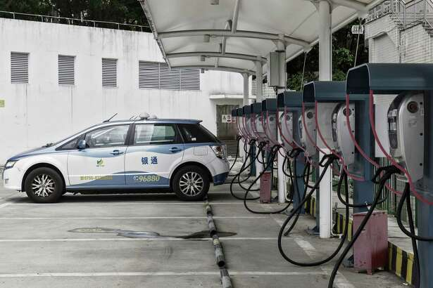 A BYD E6 electric taxi is charged at the company's charging station in Shenzhen, China, on Sept. 20, 2017.