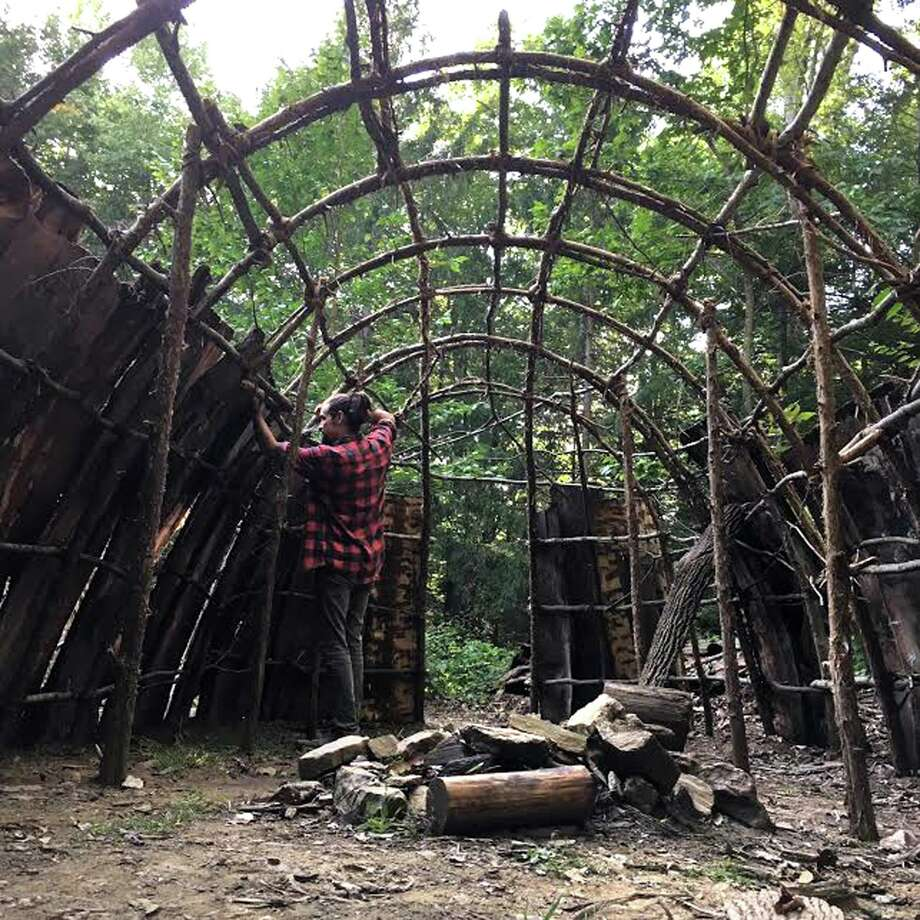 Griffin Kalin lashes bark to the longhouse fraime in the Native American village at IAIS in Washington. Photo: Lauren Bennett / Contributed Photo /
