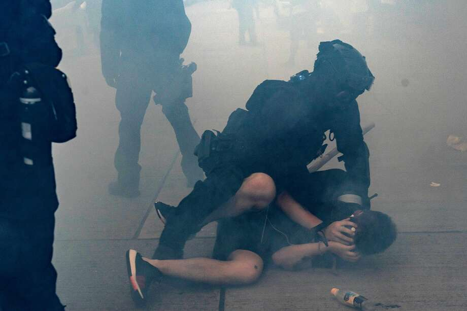 HONG KONG, CHINA - OCTOBER 20: A pro-democracy protester is arrested by riot police in a cloud of tear gas during a demonstration on October 20, 2019 in Hong Kong, China. Hong Kong's government invoked emergency powers last week to introduce an anti-mask law which bans people from wearing masks at public assemblies as the city remains on edge with the anti-government movement entering its fourth month. Protesters in Hong Kong continue to call for Chief Executive Carrie Lam to meet their remaining demands since the controversial extradition bill was withdrawn, which includes an independent inquiry into police brutality, the retraction of the word riot to describe the rallies, and genuine universal suffrage, as the territory faces a leadership crisis. (Photo by Anthony Kwan/Getty Images) Photo: Anthony Kwan / Getty Images