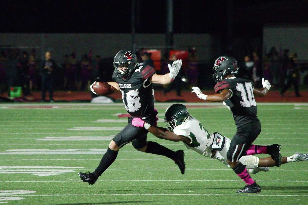 Pearland's Tanner Tullos drags Strake Jesuit's Denzel Blackwell (3) Friday at The Rig.