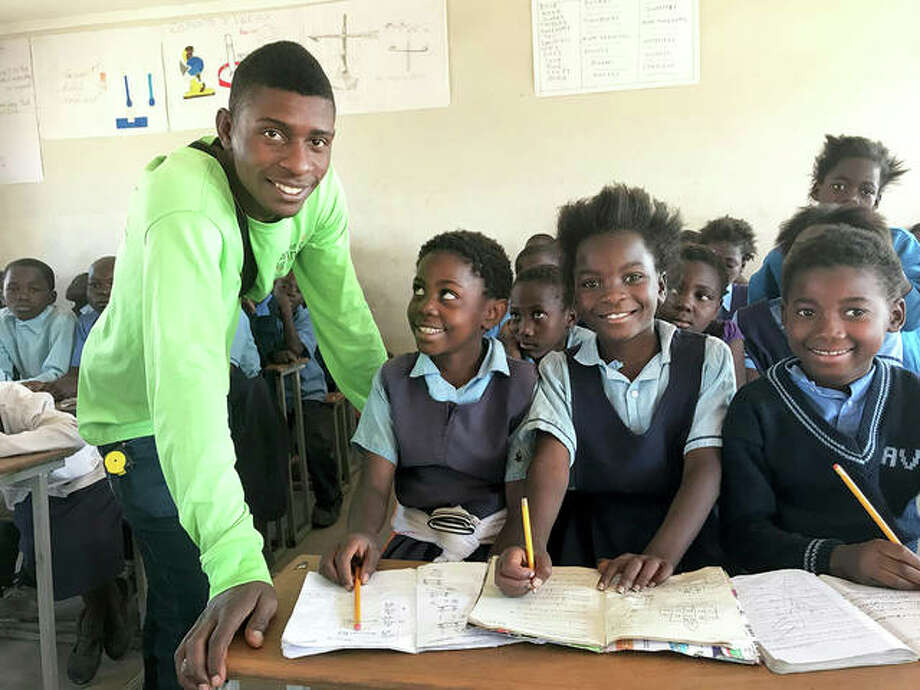 Haward, left, in a recent photo, working with African Vision of Hope students in Zambia, where he mentors younger children. Photo: Courtesy Of African Vision Of Hope