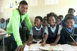 Haward, left, in a recent photo, working with African Vision of Hope students in Zambia, where he mentors younger children.