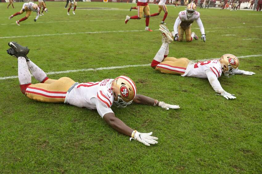 Linebacker Azeez Al-Shaair #51 of the San Francisco 49ers and teammates slide on the rain soaked field after defeating Washington, 9-0, at FedExField on October 20, 2019 in Landover, Maryland. (Photo by Patrick Smith/Getty Images)
