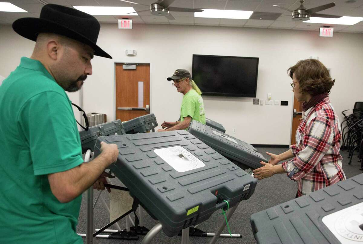 Harris County County Attorney Conference Center early voting election clerks Ignacio Zaragoza, from left, C Patrick McIlvain and Ana Coello setting up the voting machines on Friday, Oct. 18, 2019, in Houston. Early voting begins Monday ahead of the Nov. 5 election, when Houston and Harris County voters will cast ballots for mayor, city council, controller and a host of referendums and other offices.