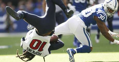 Houston Texans wide receiver DeAndre Hopkins (10) is flipped as Indianapolis Colts defensive back George Odum (30) tries to stop him in the first half at Lucas Oil Stadium on Sunday, Oct. 20, 2019 in Indianapolis.