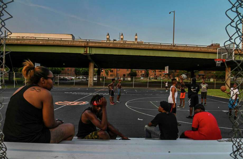 Kids play basketball at Wilson Park near where highway I-81 slices through the public housing complex called Pioneer Homes in the south side of the city in Syracuse, N.Y. If this elevated section of the highway is torn down, residents hope the state will contain construction dust that threatens to increase the neighborhood's already soaring asthma rates, which are believed to be correlated to living in close proximity to the highway and its traffic. Photo: Washington Post Photo By Jahi Chikwendiu / The Washington Post