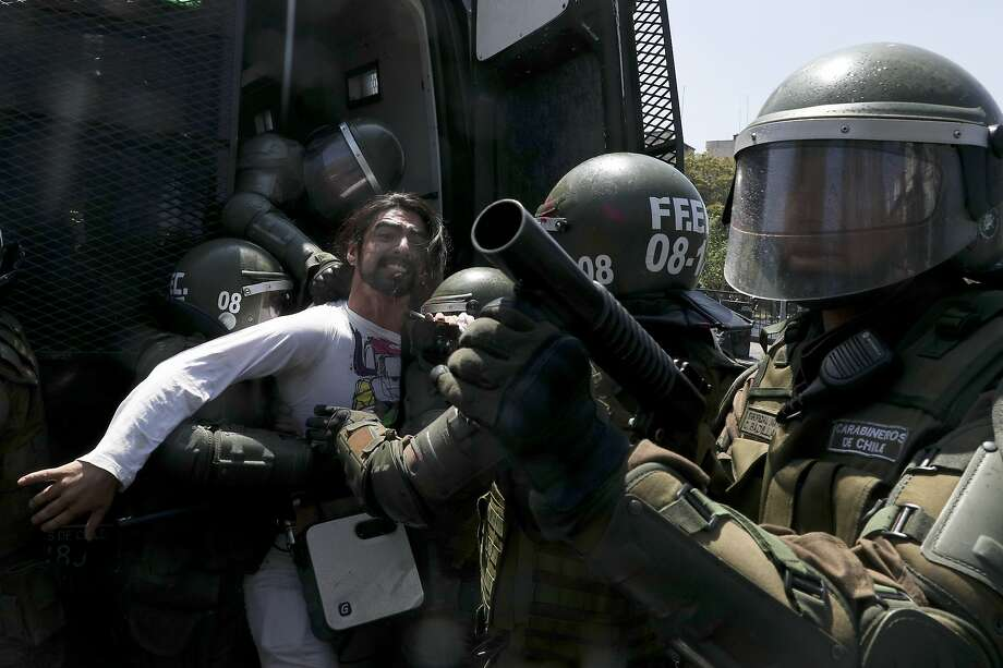 Riot police detain a demonstrator in Santiago, Chile, Sunday, Oct. 20, 2019. Protests in the country have spilled over into a new day Sunday, even after President Sebastian Pinera cancelled the subway fare hike that prompted massive and violent demonstrations. (AP Photo/Esteban Felix) Photo: Esteban Felix, Associated Press