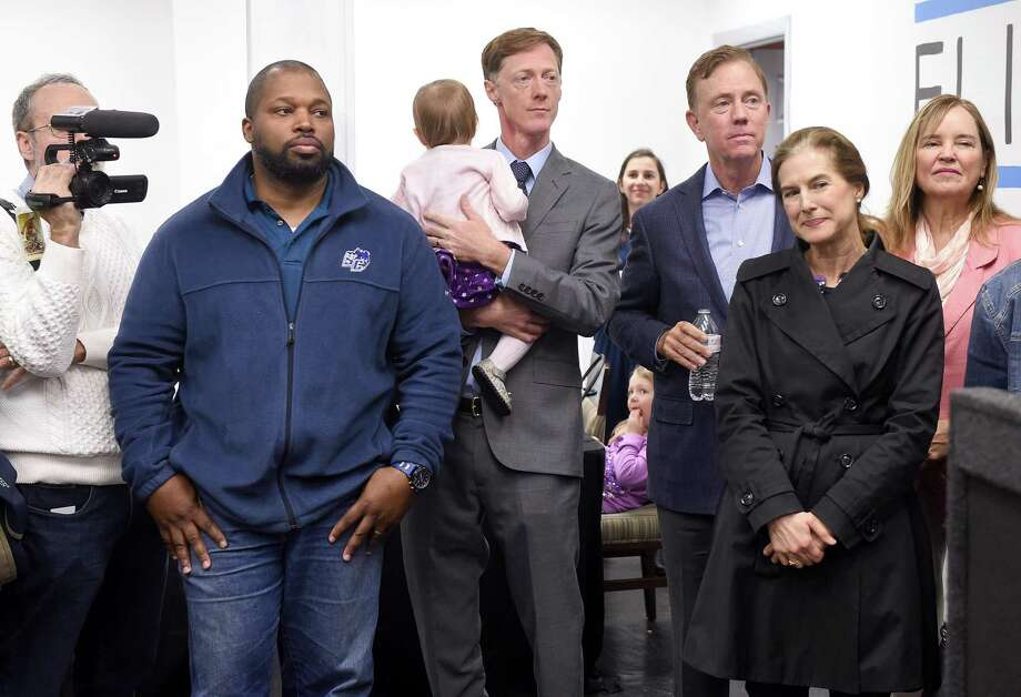 New Haven Democratic nominee for mayor Justin Elicker (center) stands holding his daughter, April, 1, flanked by State Senator Gary Winfield (left), Governor Ned Lamont (center right), Lt. Governor Susan Bysiewicz (right) and Connecticut Secretary of State Denise Merrill (far right) listens to speakers at a unity rally for Elicker in New Haven on October 20, 2019. At left is Stanley Heller, executive director of the Middle East Crisis Committee. Photo: Arnold Gold / Hearst Connecticut Media / New Haven Register