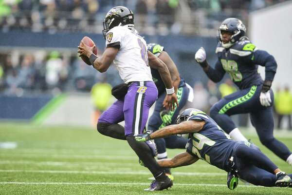 Baltimore Ravens quarterback Lamar Jackson (8) evades a tackle attempt by Seattle Seahawks cornerback Jamar Taylor (24) in the second quarter of Seattle's game against Baltimore, Sunday, Oct. 20, 2019 at CenturyLink Field.