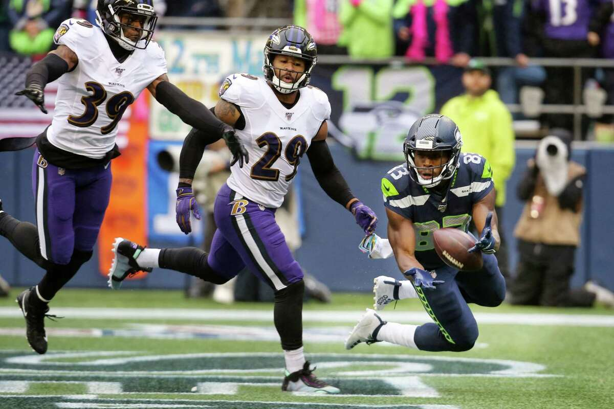 A touchdown pass slips through the hands of Seattle Seahawks wide receiver David Moore (83) as Ravens cornerback Brandon Carr (39) and safety Earl Thomas (29) defend in the second quarter of Seattle's game against Baltimore, Sunday, Oct. 20, 2019 at CenturyLink Field.