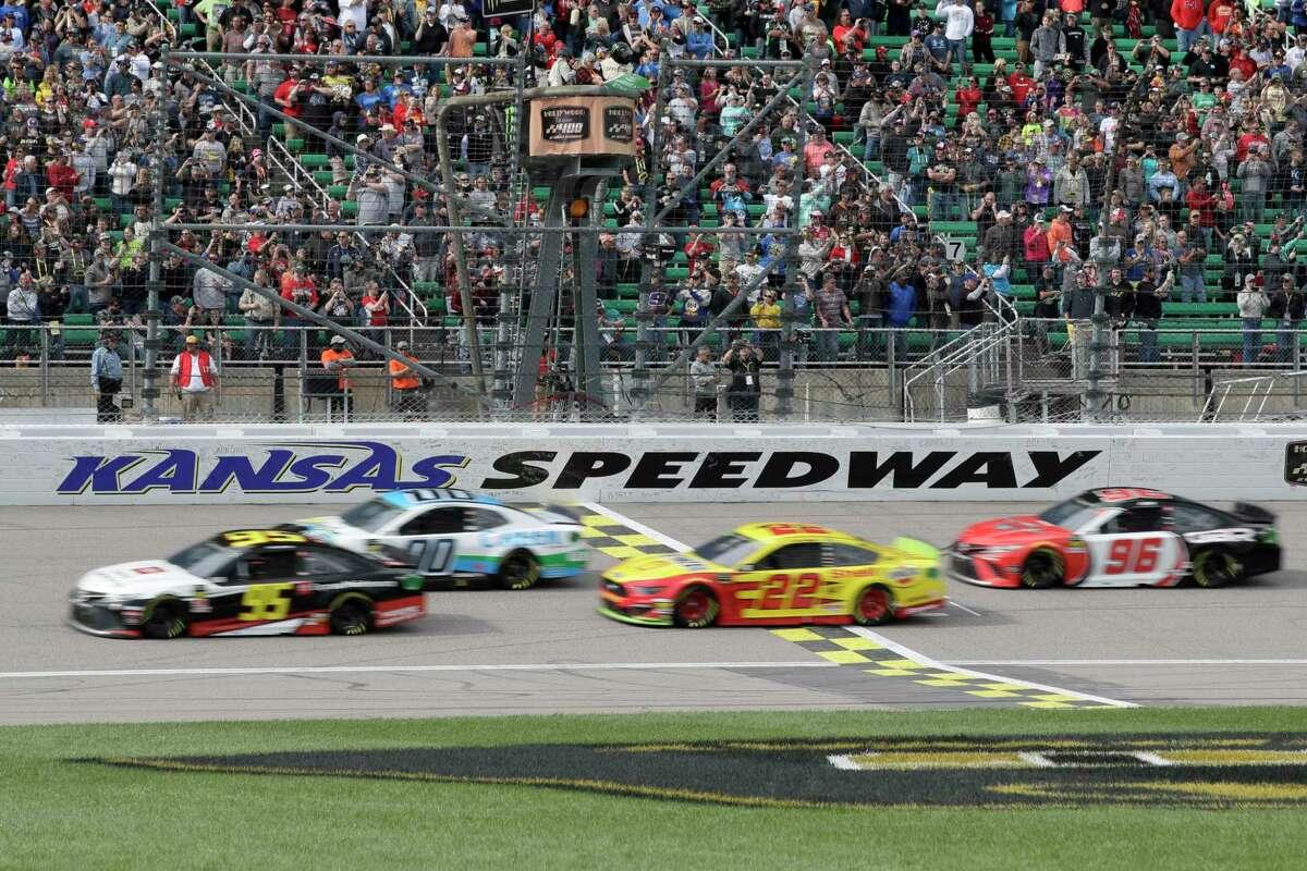 Matt DiBenedetto (95), Landon Cassill (00), Joey Logano (22) and Parker Kligerman (96) take the green flag during a NASCAR Cup Series auto race at Kansas Speedway in Kansas City, Kan., Sunday, Oct. 20, 2019. (AP Photo/Orlin Wagner)