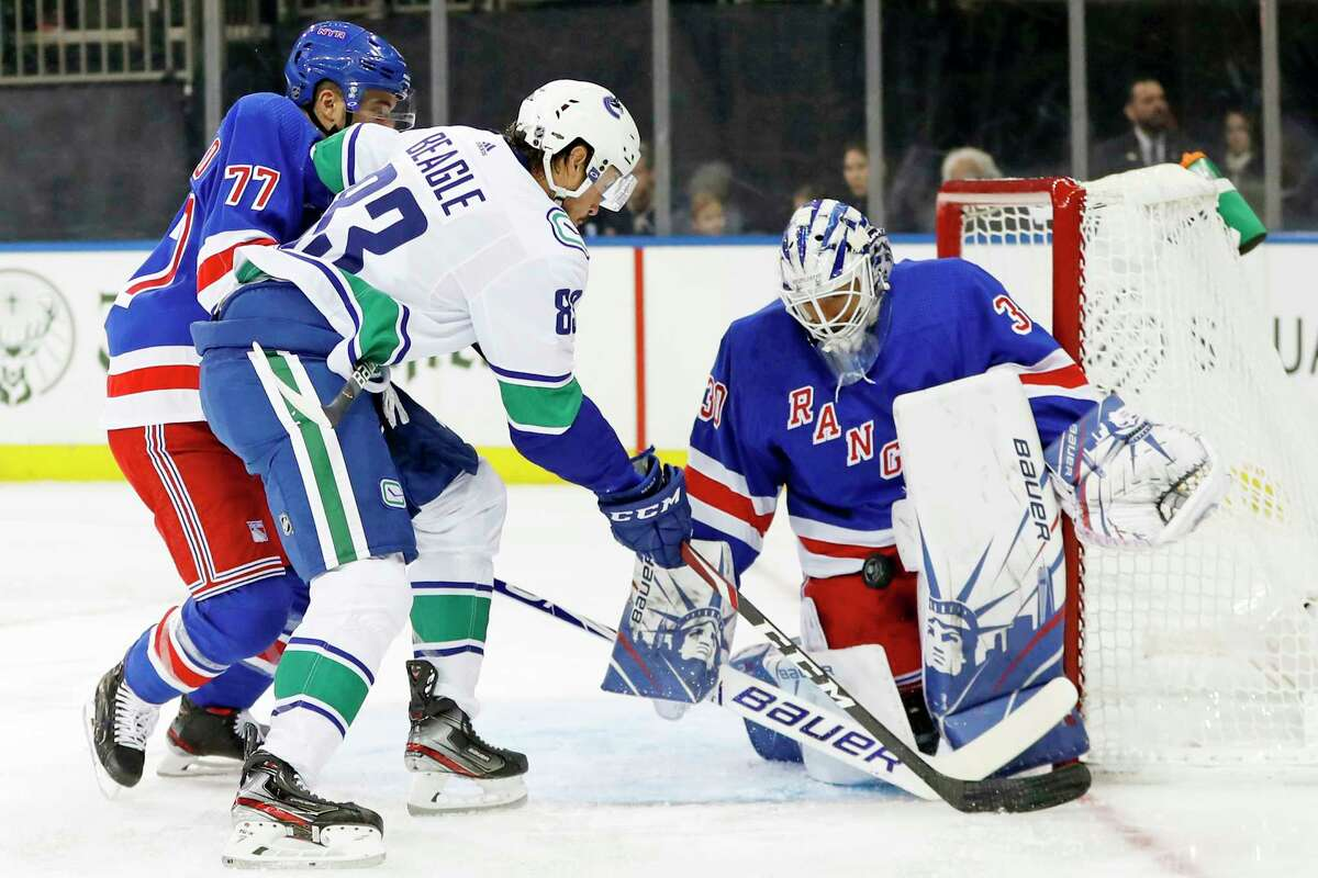 New York Rangers goaltender Henrik Lundqvist (30) of Sweden blocks a shot as Vancouver Canucks center Jay Beagle (83) tries to score with Rangers defenseman Tony DeAngelo (77) defending in the first period of a NHL hockey game, Sunday, Oct. 20, 2019, in New York. (AP Photo/Kathy Willens)