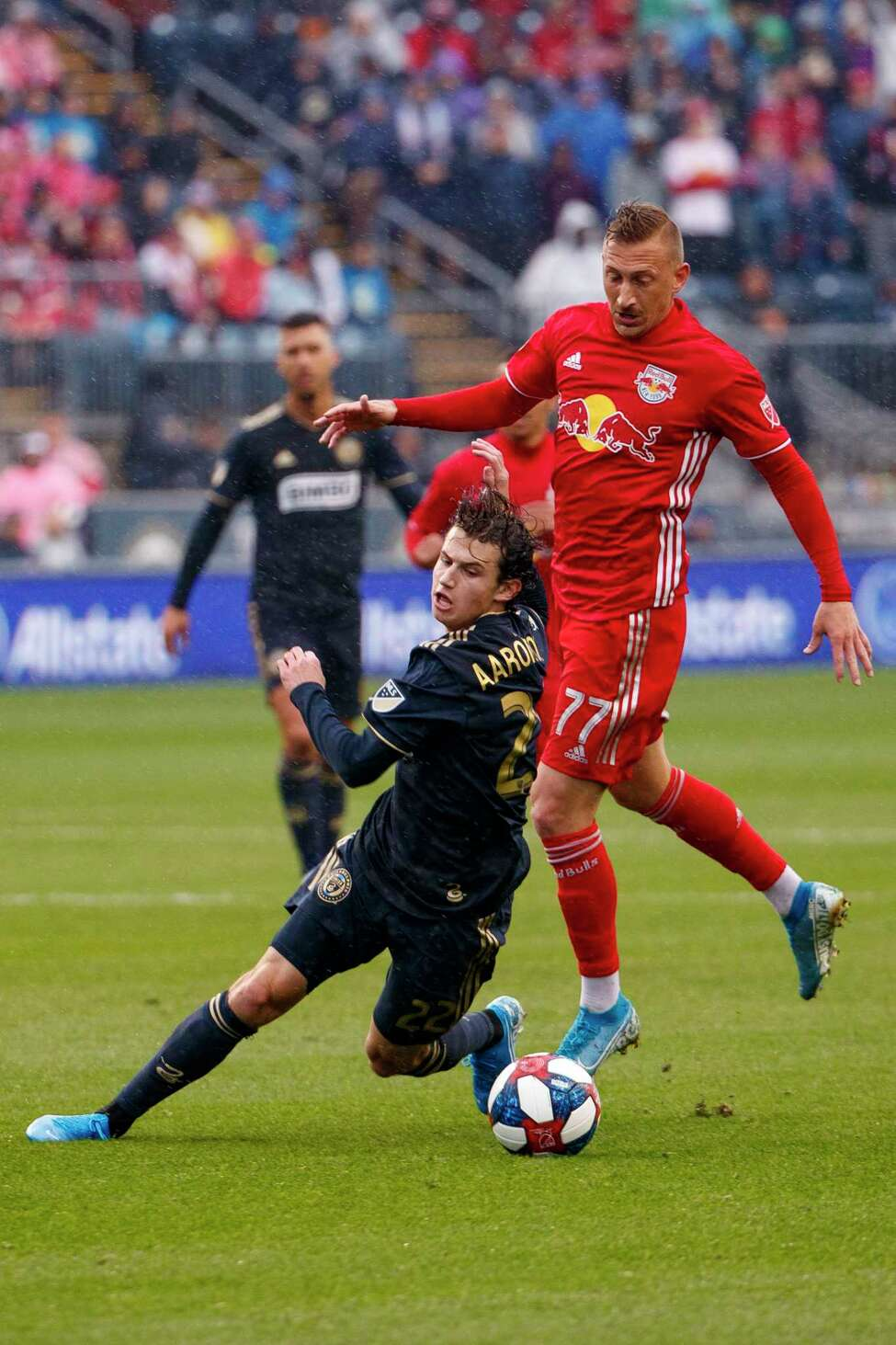 Philadelphia Union's Brenden Aaronson, left, goes after the ball against New York Red Bulls' Daniel Royer, right, during first half of an MLS soccer Eastern Conference first-round playoff match, Sunday, Oct. 20, 2019, in Chester, Pa. (AP Photo/Chris Szagola)