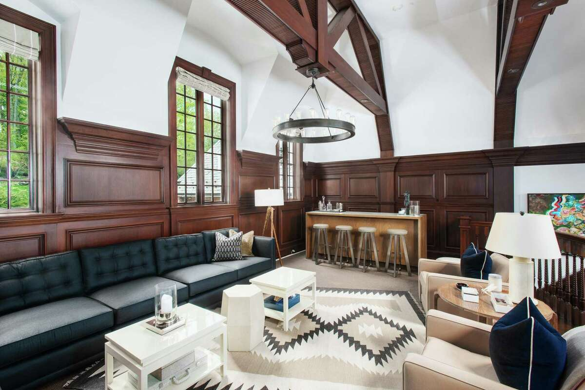 At the Georgian colonial estate at 7 Topping Road, the great room has a bar area of its own. The magnificent entertaining space has a trussed ceiling, mahogany paneling, a fireplace and access out to the terrace. The 4.6-acre Topping Lake estate is listed by Houlihan Lawrence for $9.95 million.