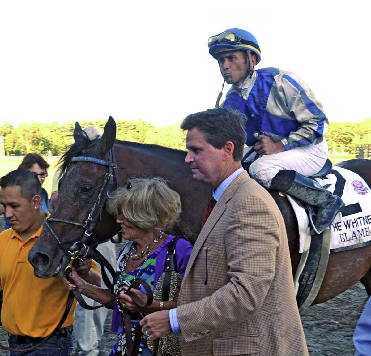 Owner Adele Dilschneider and trainer Albert Stall lead Garrett Gomez and Blame to the winner's circle after winning the 83rd running of The Whitney Stakes at Saratoga Race Course on Aug. 7, 2010.