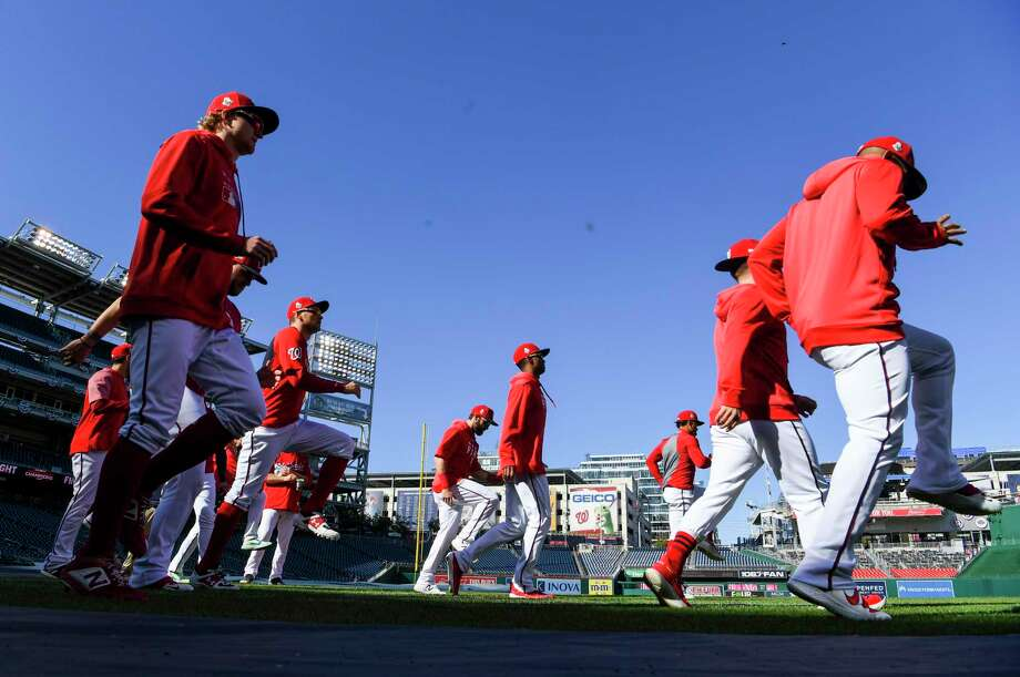 Members of the Washington Nationals warm up as they prepare for the World Series during a workout at Nationals Park on Oct. 18, 2019. Photo: Washington Post Photo By Jonathan Newton / The Washington Post