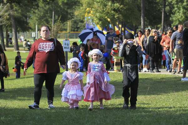 Cody LeBlanc, walks toward the playground dressed as a ninja beside his sisters Fifi and Scottie during the Trick or Treat Trail at Carol Barton, Jr. Park, Saturday, Oct. 19, 2019, in Conroe. The annual event drew hundreds of children for candy and other family activates.