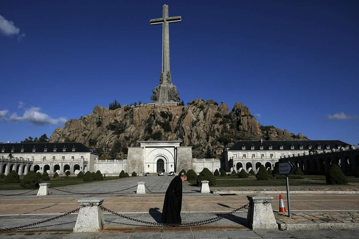 In this photo taken on Sunday, Oct. 13, 2019, A friar walks in front of The Valley of the Fallen mausoleum near El Escorial, outskirts of Madrid, After a tortuous judicial and public relations battle, Spain's Socialist government has announced that Gen. Francisco Franco's embalmed body will be relocated from a controversial shrine to a small public cemetery where the former dictator's remains will lie along with his deceased wife. (AP Photo/Manu Fernandez)
