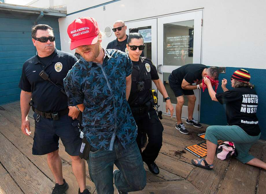 A supporter of President Donald Trump is arrested after a clash with anti-Trump protesters during a rally against his policies in Santa Monica, California on October 19, 2019. - Several people were arrested after fighting and pepper spray was used by the opposing groups. Photo: Mark Ralston, AFP Via Getty Images
