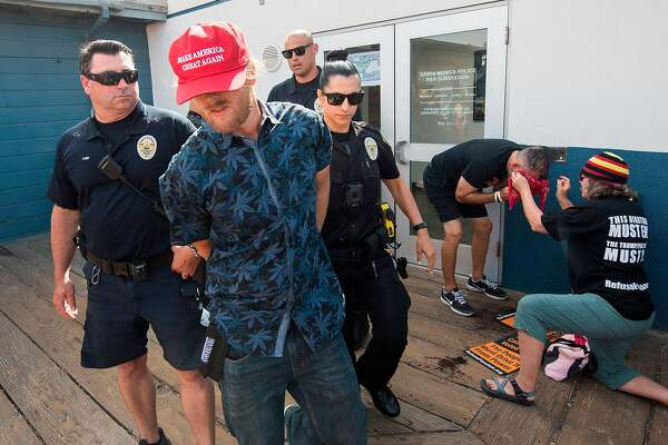 A supporter of President Donald Trump is arrested after a clash with anti-Trump protesters during a rally against his policies in Santa Monica, California on October 19, 2019. - Several people were arrested after fighting and pepper spray was used by the opposing groups. (Photo by Mark RALSTON / AFP) (Photo by MARK RALSTON/AFP via Getty Images)