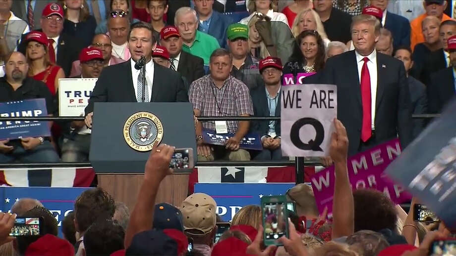 President Donald Trump attends a campaign rally for Ron DeSantis, left, at the Florida State Fairgrounds Expo Hall on July 31, 2018, in Tampa. Signs were seen in the crowd referencing QAnon, a conspiracy theory. Photo: The Washington Post / The Washington Post