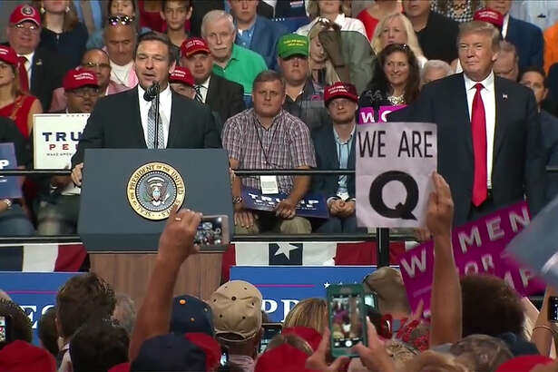 President Donald Trump attends a campaign rally for Ron DeSantis, left, at the Florida State Fairgrounds Expo Hall on July 31, 2018, in Tampa. Signs were seen in the crowd referencing QAnon, a conspiracy theory.