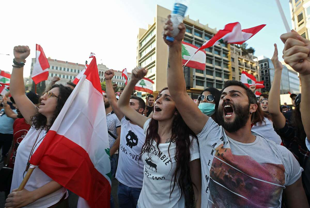 Lebanese protesters take to the streets during demonstrations to demand better living conditions and the ouster of a cast of politicians who have monopolised power and influence for decades, on October 21, 2019 at Riad al-Solh Square in Beirut. - Lebanon's teetering government met today to approve a belated economic rescue plan as thousands gathered for a fifth day of mass protests against the ruling elite. (Photo by Anwar AMRO / AFP) (Photo by ANWAR AMRO/AFP via Getty Images)