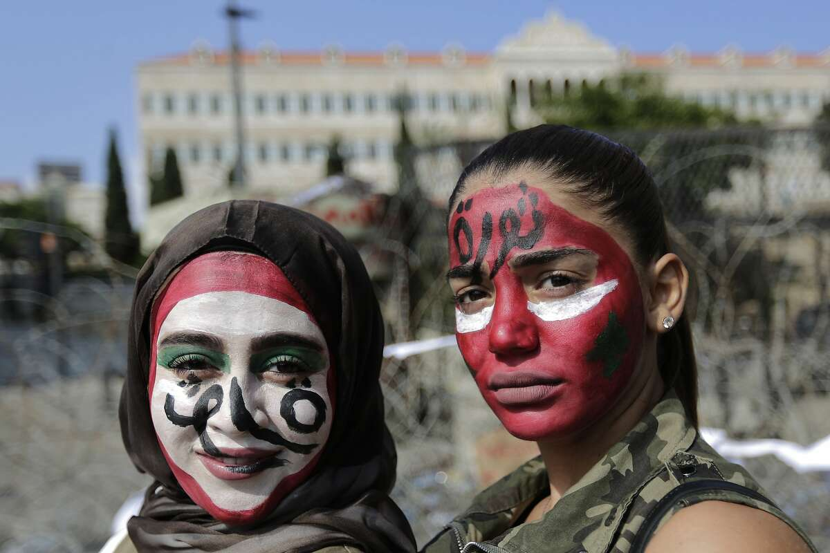 Anti-government protesters with the colors of the Lebanese national flag painted on their faces and with Arabic that reads