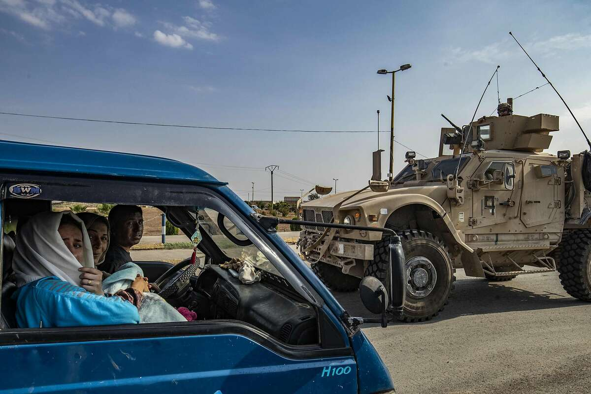 TOPSHOT - A US military vehicle drives on a road after US forces pulled out of their base in the Northern Syriain town of Tal Tamr on October 20, 2019, as members of a Syrian family fleeing the countryside of Ras al-Ain head north in a van to the region of al-Hasakeh. - US forces withdrew from a key base in northern Syria today, a monitor said, two days before the end of a US-brokered truce to stem a Turkish attack on Kurdish forces in the region. (Photo by Delil SOULEIMAN / AFP) (Photo by DELIL SOULEIMAN/AFP via Getty Images)