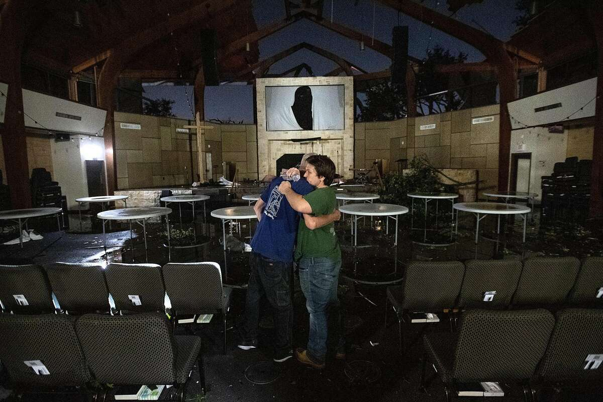 In this Sunday, Oct. 20, 2019 photo, Matt Younger, right, a pastor at Northway Church, embraces facilities associate Robert Lusk in their church's severely damaged sanctuary after a tornado tore through North Dallas. (AP Photo/Jeffrey McWhorter)
