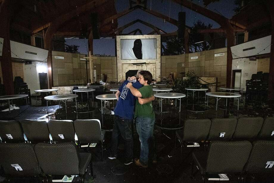 In this Sunday, Oct. 20, 2019 photo, Matt Younger, right, a pastor at Northway Church, embraces facilities associate Robert Lusk in their church's severely damaged sanctuary after a tornado tore through North Dallas. (AP Photo/Jeffrey McWhorter) Photo: Jeffrey McWhorter / Associated Press