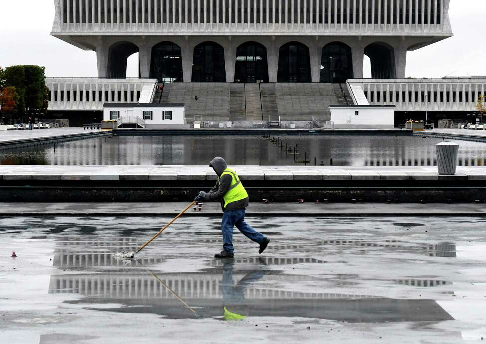 Workers with the Office of General Services clean the Empire State reflecting pool across from the Capitol on Monday, Oct. 21, 2019, in Albany N.Y. The shallow pool is used as a skating rink during winter months. (Will Waldron/Times Union)