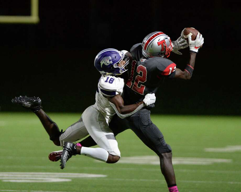 Mike Samba (12) of Travis makes a reception with Jonathan James (18) of Ridge Point in coverage during the fourth quarter of a 6A Region III District 20 football game between the Ridge Point Panthers and Travis Tigers on Thursday, October 17, 2019 at Mercer Stadium, Sugar Land, TX. Photo: Craig Moseley, Houston Chronicle / Staff Photographer / ©2019 Houston Chronicle