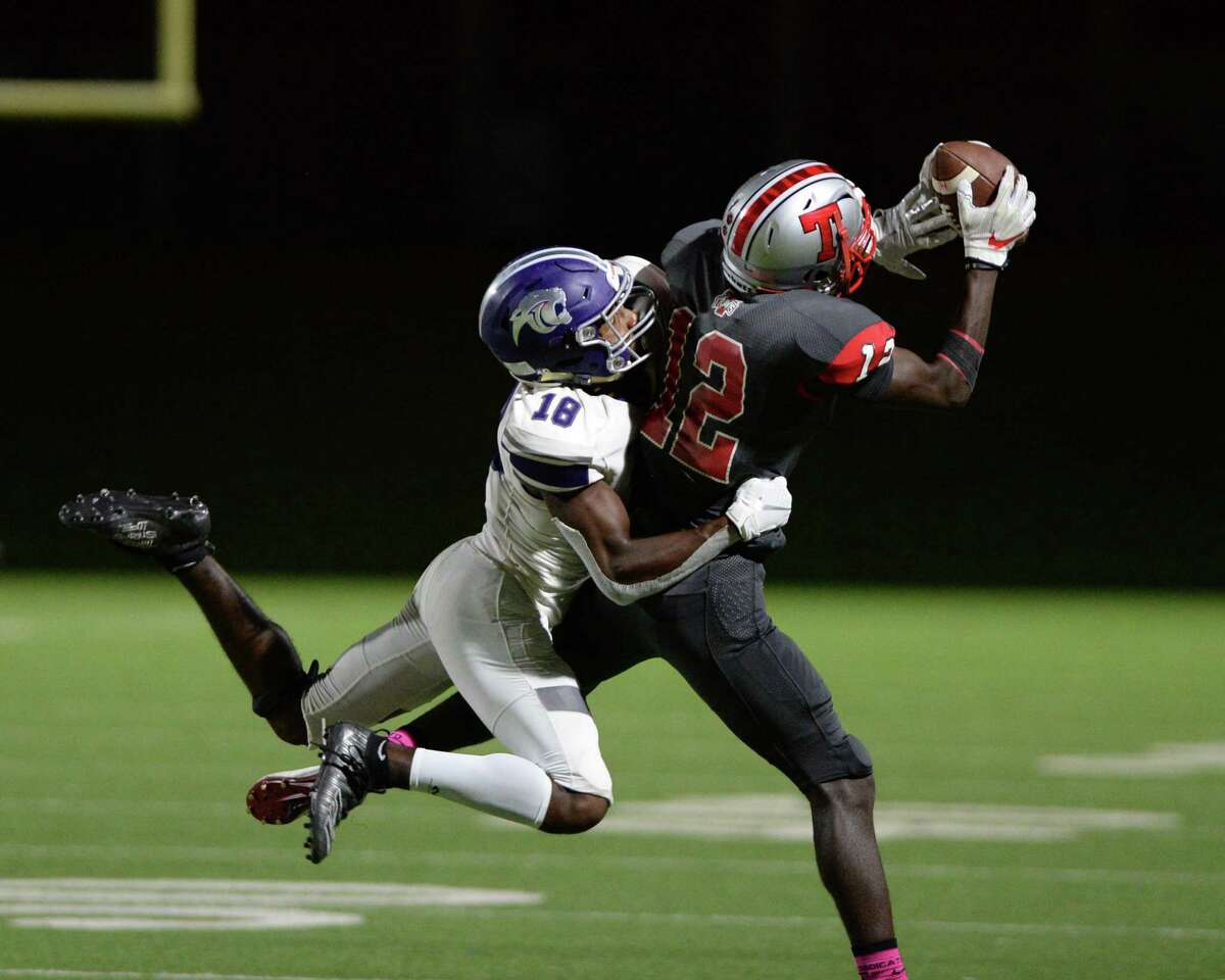 Mike Samba (12) of Travis makes a reception with Jonathan James (18) of Ridge Point in coverage during the fourth quarter of a 6A Region III District 20 football game between the Ridge Point Panthers and Travis Tigers on Thursday, October 17, 2019 at Mercer Stadium, Sugar Land, TX.