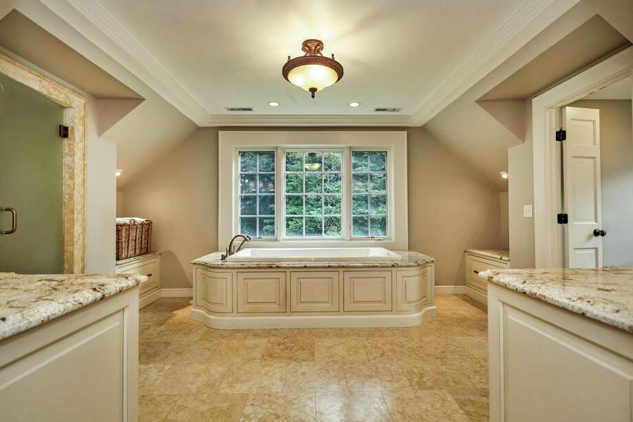 The spacious, luxurious master bath features a heated limestone floor, two granite vanities, a large limestone steam shower, air-jetted tub, and water closet.