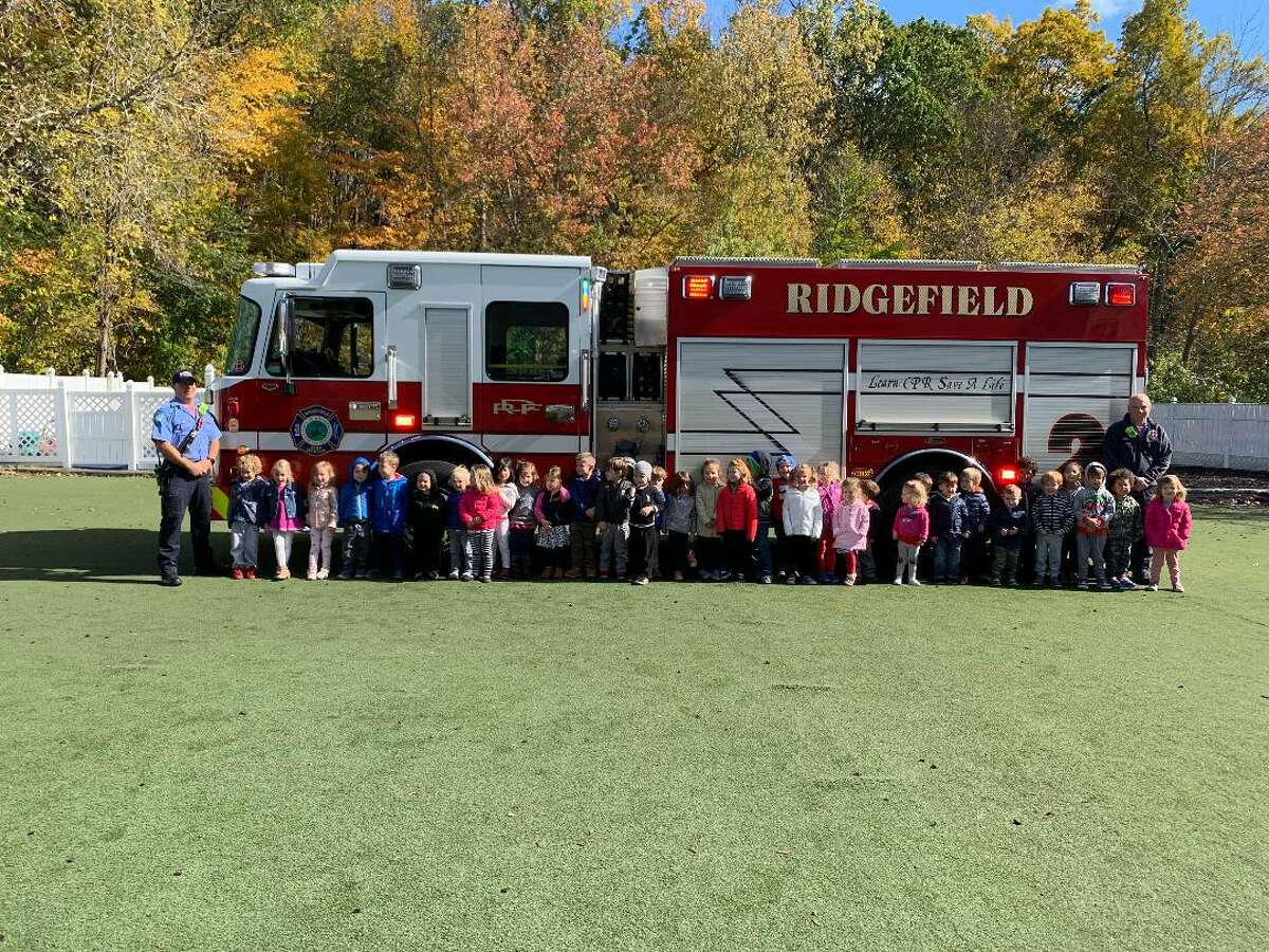 """On Friday October 18, two Ridgefield Fire Department firefighters came out to speak to the children about fire safety and the importance of dialing 911 in an emergency. The firefighters also showed the children how they put on their gear and demonstrated the equipment. """"We would like to thank the Ridgefield Fire Department for coming to Children's Academy,"""" said Peggy Define."""