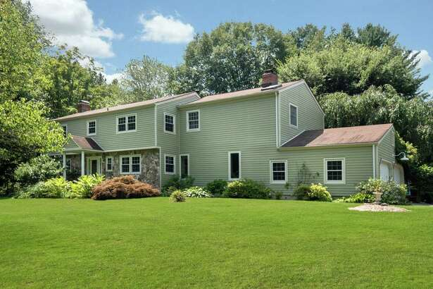 The stone and sage-colored colonial house at 146 Old Hyde Road Extension in Lower Weston sits on a two-acre mini farm property.