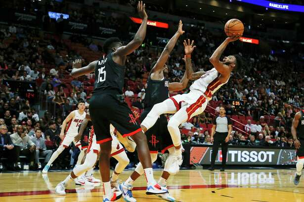 Miami Heat forward Derrick Jones Jr. (5) falls backward while shooting under pressure from Houston Rockets center Clint Capela (15) and forward Danuel House Jr. during the third quarter of an NBA preseason basketball game Friday, Oct. 18, 2019, in Miami. The Rockets won 144-133.