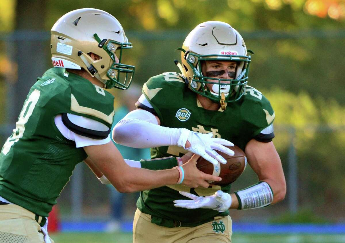 Notre Dame of West Haven QB Jackson Zalinsky hands the ball off to Mark Altieri during football action against Amity in West Haven, Conn., on Friday Oct. 4, 2019.