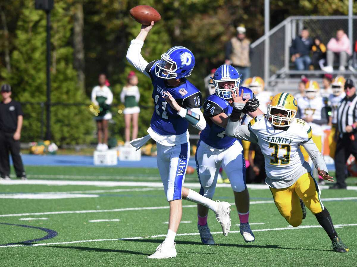 Darien's Peter Graham (11) throws a pass while Trinity Catholic's Rocco Cuscuna (33) pressures during a football game at Darien High School on Saturday, Oct. 19, 2019.