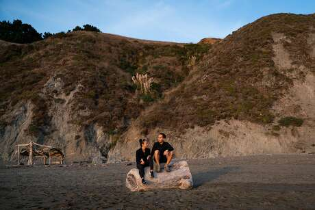 Katherine Disenhof of Portland, left, and Alan Ibrahim of San Francisco, sit to watch the sunset at Goat Rock Beach in Sonoma County, Calif. on Saturday, Oct. 12, 2019.
