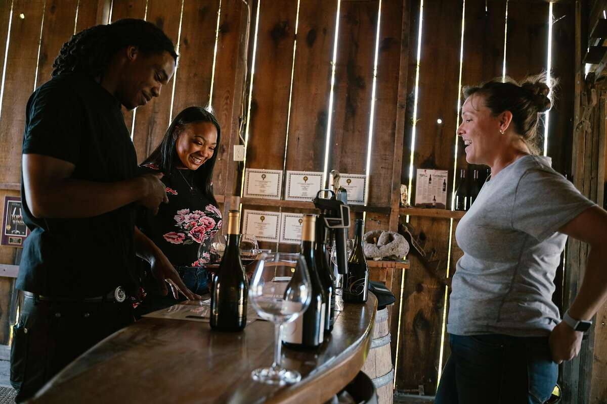 (Left to right) Theus Lane, 24, of Sacramento, and Infinity Price, 23, of Fairfield, have a private wine tasting session with Christine Fife at Canihan Winery in Sonoma, Calif. on Sunday, Oct. 13, 2019.