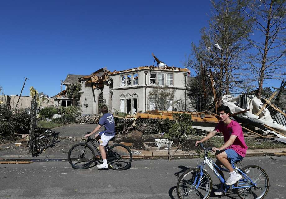 Bicyclists ride past a house damaged by a tornado in the Preston Hollow section of Dallas, Monday, Oct. 21, 2019. Photo: (AP Photo/LM Otero) / Copyright 2019 The Associated Press. All rights reserved.