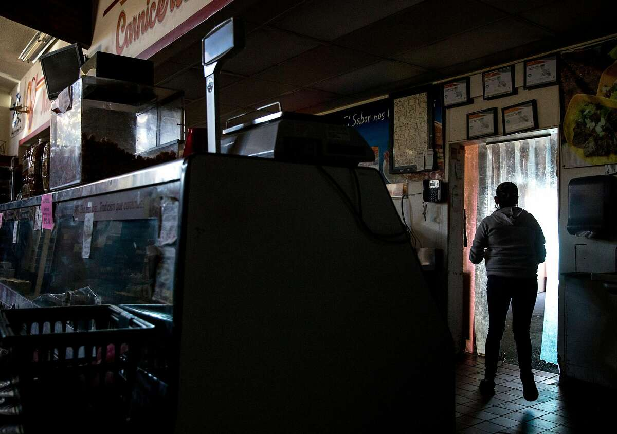 An employee works in the dark behind the deli counter of La Tapatia Market in Napa, Calif. Wednesday, Oct. 9, 2019 following the first stage of PG&E Public Safety Power Shutoffs across Northern California.
