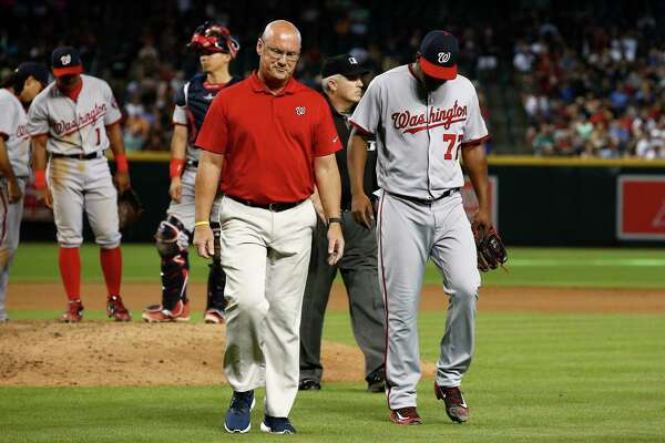 An injured Enny Romero, right, walks off the field with Nationals trainer Paul Lessard during a 2017 game in Phoenix.
