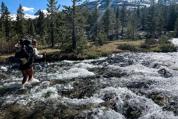 Thru-hiker Elise Ott fording a river on the Pacific Crest Trail in the Sierra in 2019.